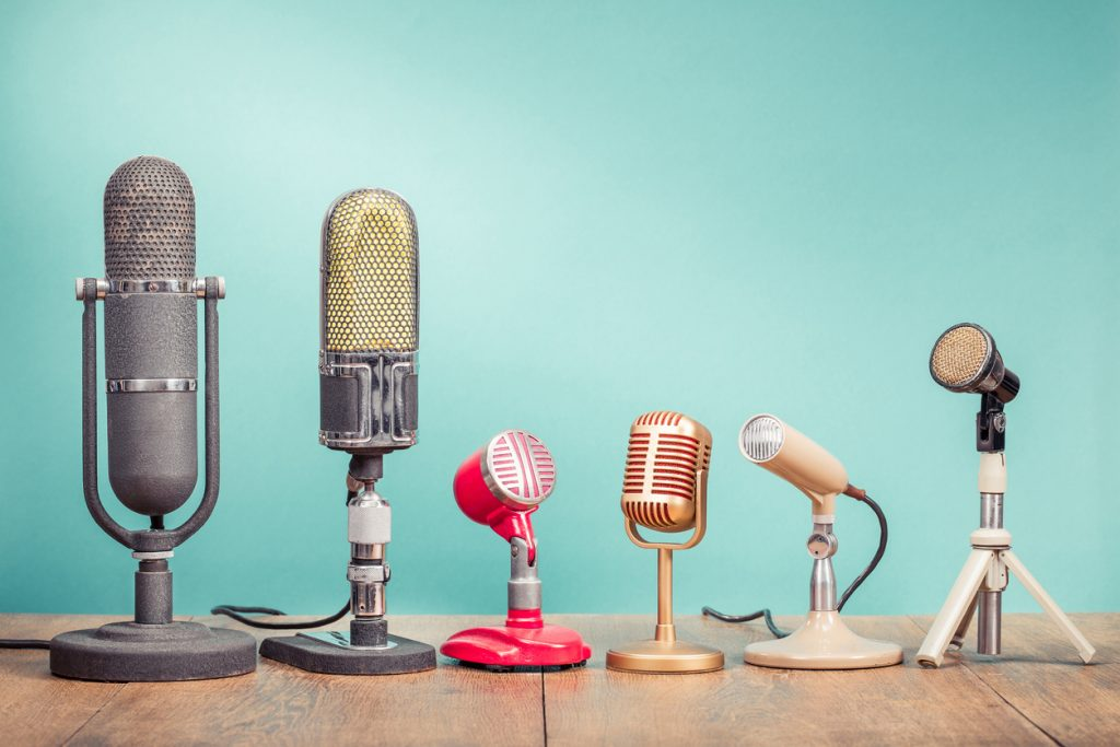 Retro old microphones for press conference or interview recording on table front gradient aquamarine background.